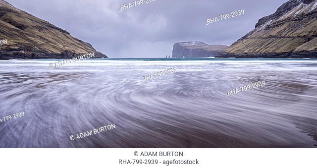 Waves crash against the black sandy beach at Tjornuvik on the island of Streymoy, Faroe Islands, Denmark, Europe