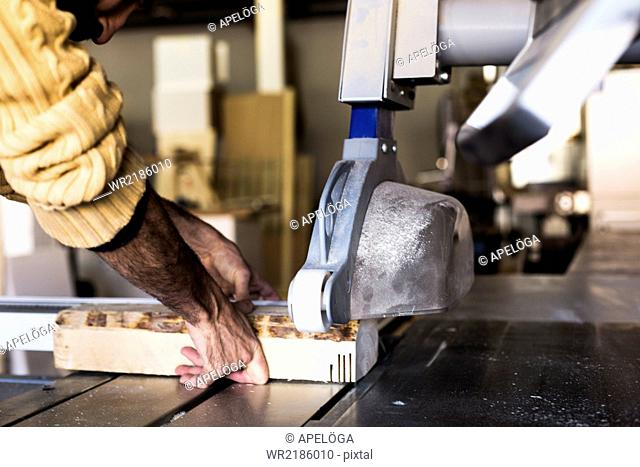 Carpenter cutting wood using table saw in workshop
