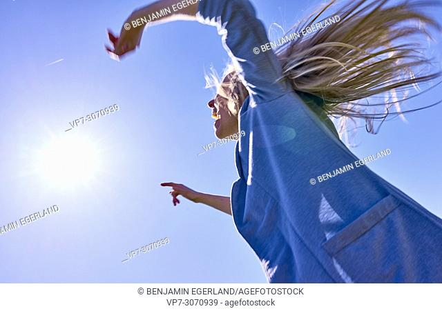 Vibrant woman shaking hair, enjoying sunny weather, against blue sky, full of energy. Waakirchen, Bavaria, Germany