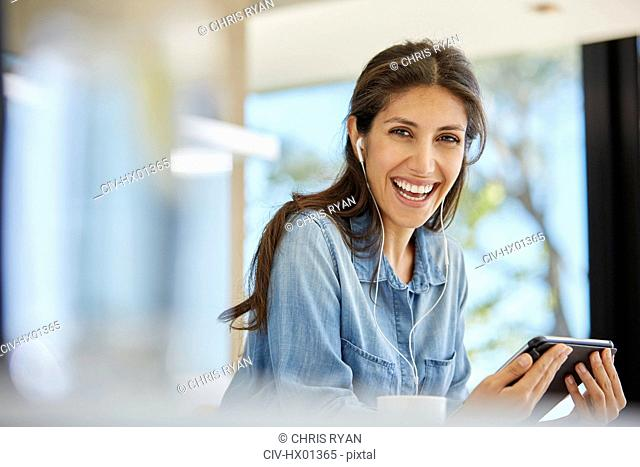 Portrait enthusiastic woman using digital tablet and headphones