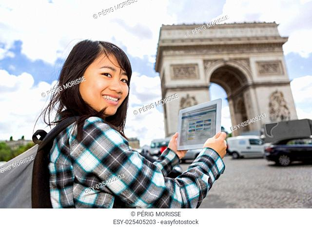 View of a Young attractive asian tourist using tablet in Paris