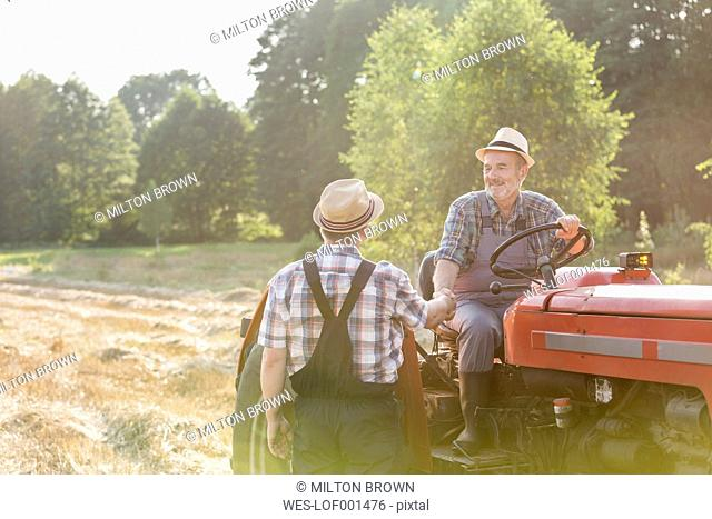 Two farmers with tractor on field shaking hands