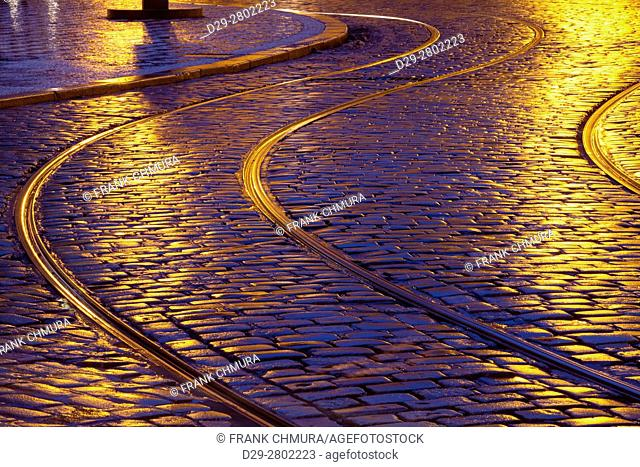 prague - tram tracks and cobblestone street at dusk after rain