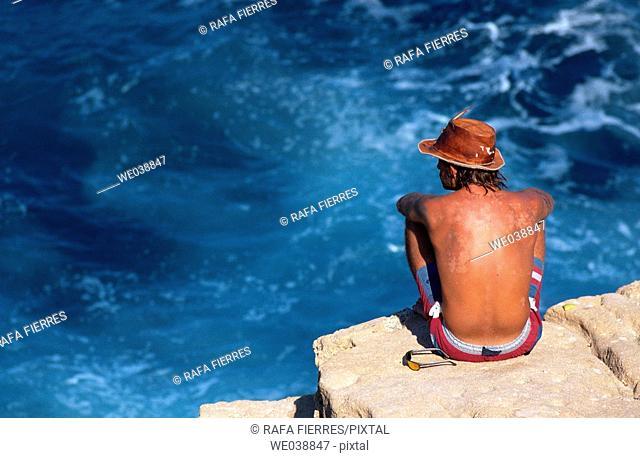 Man sunbathing on a cliff