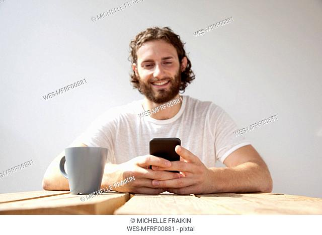 Portrait of smiling man sitting with coffee mug on balcony using cell phone