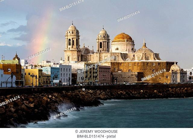 Rainbow over domes of ornate cathedral on waterfront, Cadiz, Andalusia, Spain
