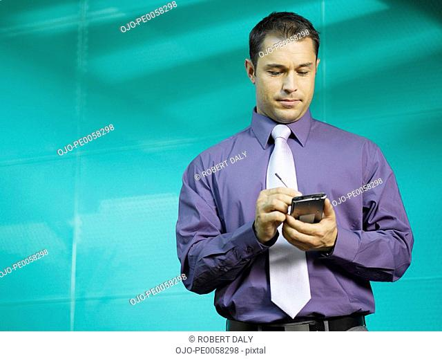Businessman using PDA in blue office