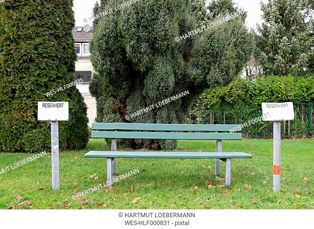 Germany, Aachen, empty bench with reserved signs