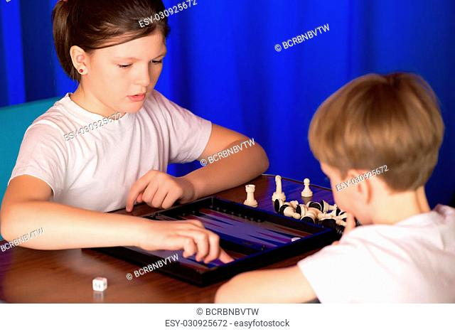 boy and girl playing in the ancient oriental game called Backgammon