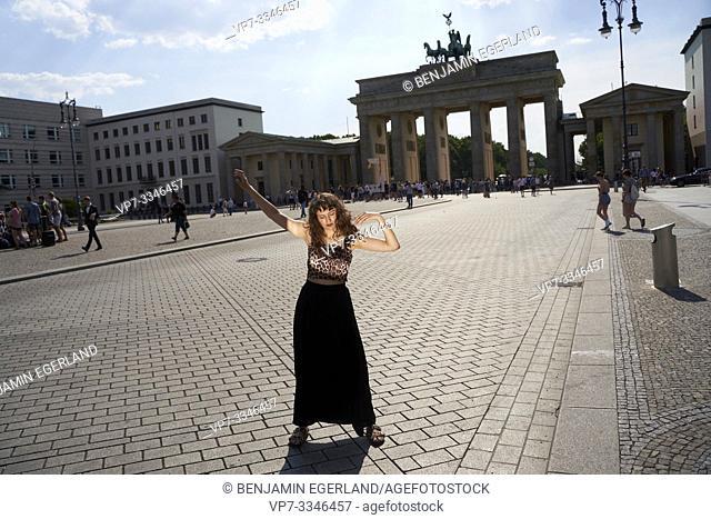 young sensual woman dancing in front of Brandenburg Gate, Brandenburger Tor, in Berlin, Germany
