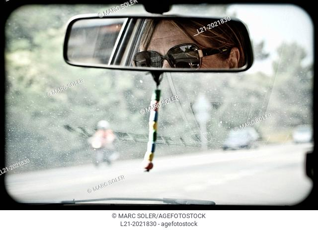 Detail of a woman wearing sunglasses in the rearview mirror of a car. Blurry vision of the road and vehicles through the windshield