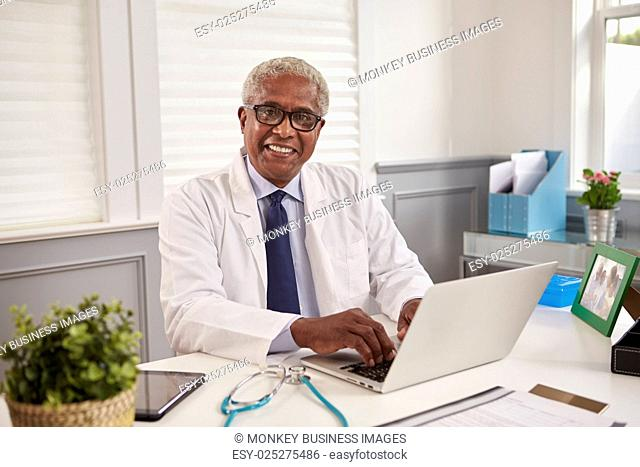 Senior black male doctor at an office desk looking to camera