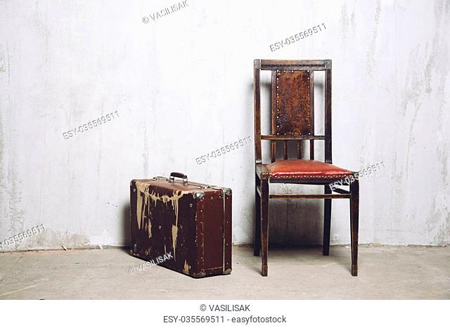 old suitcase and the old leather chair near the gray textured wall