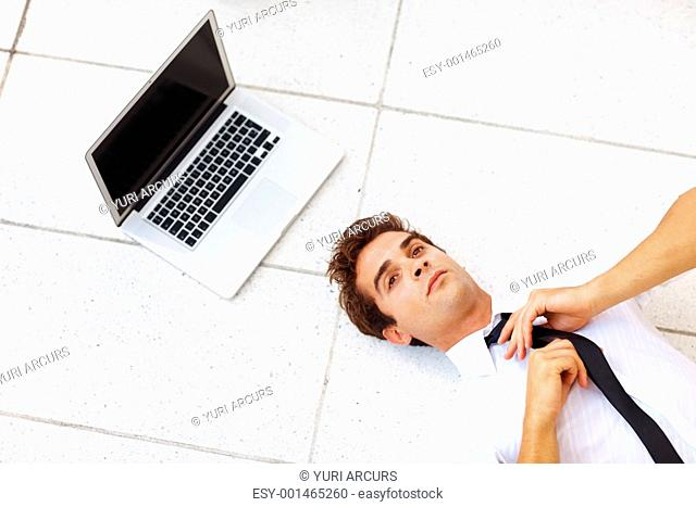 Top view of young businessman fixing his tie while lying on floor with a laptop