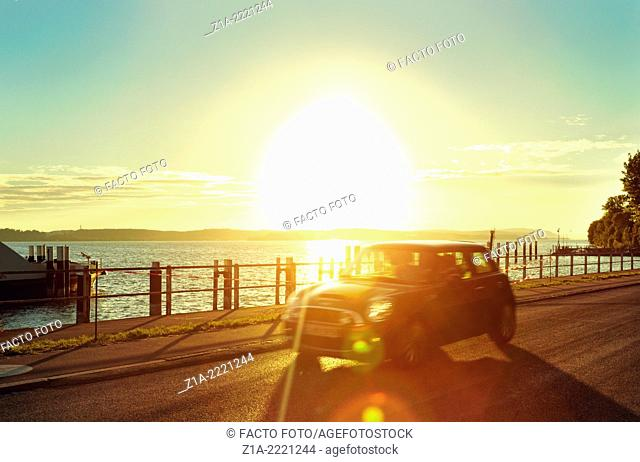 Car travelling by sunset at Lake Constance. Meersburg. Baden-Württemberg, Germany