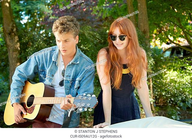 Young couple playing acoustic guitar