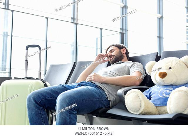 Man with teddy at airport departure area