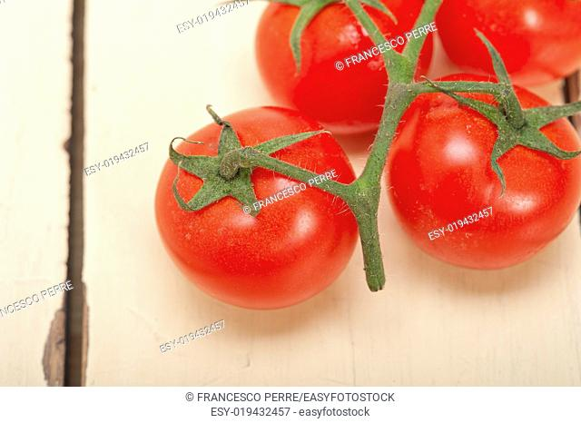fresh cherry tomatoes on a cluster over rustic wood table