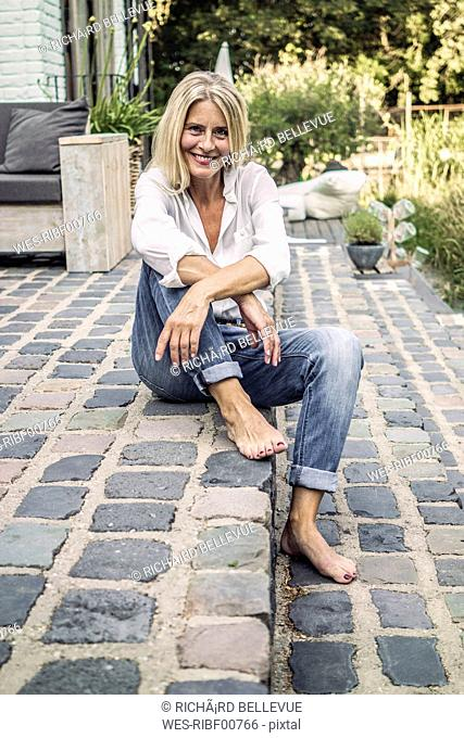 Mature woman sitting on stairs of her garden terrace