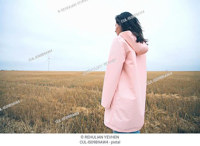 Woman in raincoat on field, Odessa, Ukraine