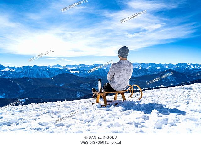 Germany, Bavaria, Brauneck, man in winter in the mountains having a break