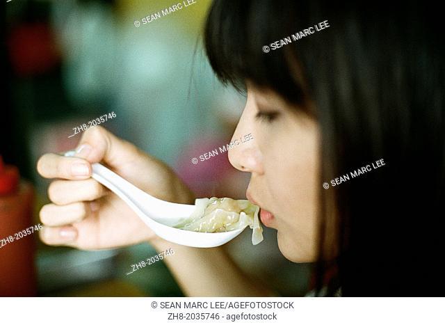 A woman about to eat a won ton soup dumpling in Kaohsiung, Taiwan