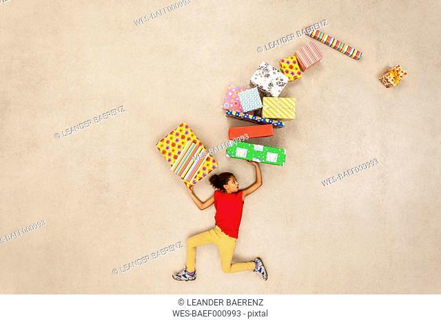 Girl balancing stack of birthday presents