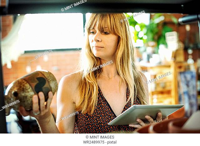 Woman in a shop, holding a digital tablet and small ceramic vase