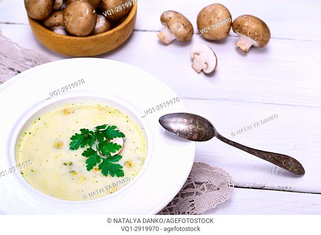 Cream mushroom soup of fresh champignons in a round white plate with an iron spoon