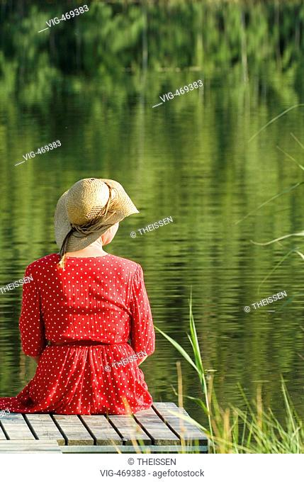 backview of a woman in red dress with sun hat sitting on wooden footbridge at a lake. - 01/01/2007