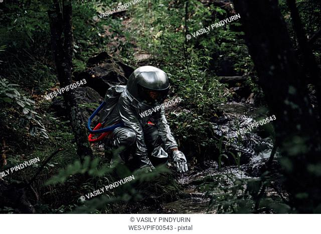 Spaceman exploring nature, crouching at a brook in forest