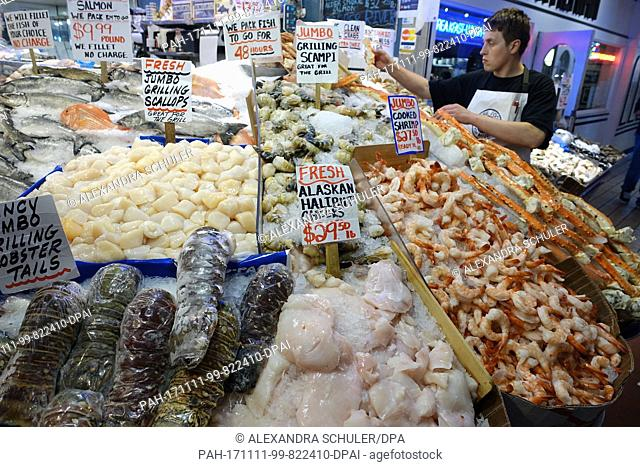 A vendor arranges the goods at a fish stand in the area of the Pike Place Market in Seattle, United States, 30 August 2017
