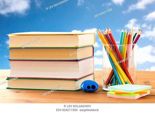 education, school, creativity and object concept - close up of crayons or color pencils with books, stickers and sharpener on wooden table over blue sky and...