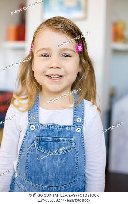 portrait of three years old blonde girl, with blue jeans dress or dungarees, standing indoor house, looking and smiling. Vertical shot