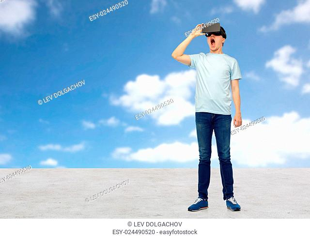 3d technology, virtual reality, entertainment, cyberspace and people concept - amazed young man with virtual reality headset or 3d glasses looking at something...