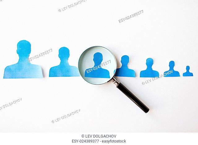 business, employment, population, career and hiring concept - close up of paper people shapes and magnifying glass on white board