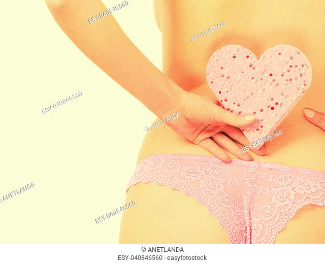 Skincare hygiene health and body care. Closeup sensual woman wearing panties holding heart shaped bath sponge in hand next to hips, toned image