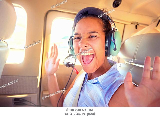 Portrait enthusiastic young woman with headphones riding in airplane