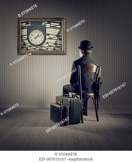 Business man sitting on old chair, checking time for his travel