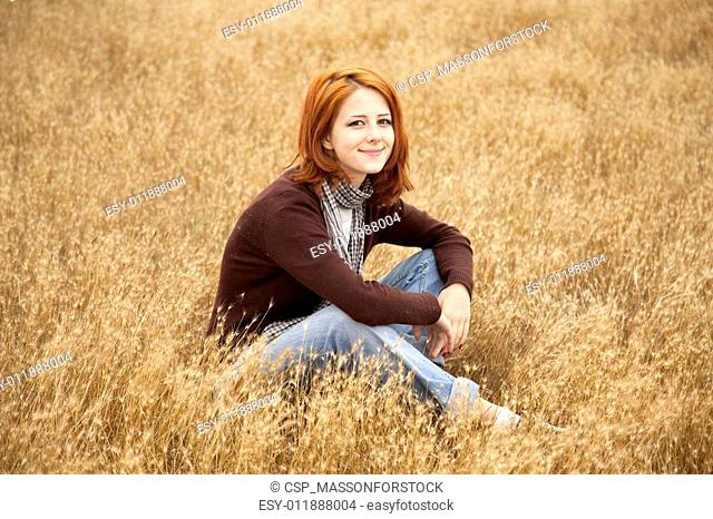 Beautiful red-haired girl at yellow autumn grass