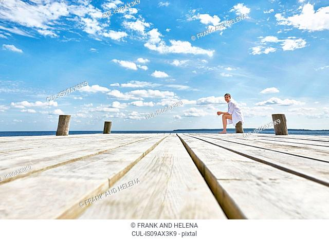 Young woman sitting on post on wooden pier, relaxing