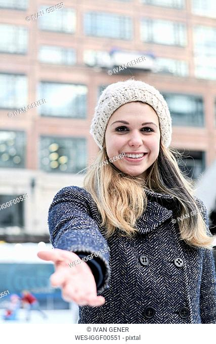 Pretty blond young woman wearing wool cap in winter, reaching out hand