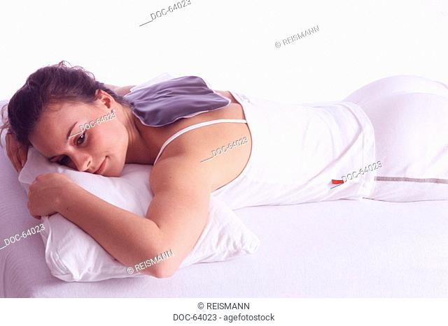 Woman with mud pillow on her neck against muscle pains