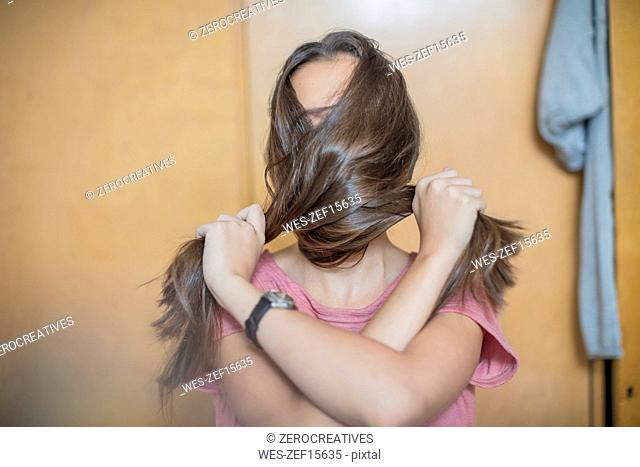 Teenage girl covering her face with her hair