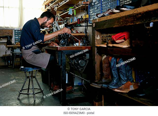 Male cobbler in traditional shoe workshop at sewing machine