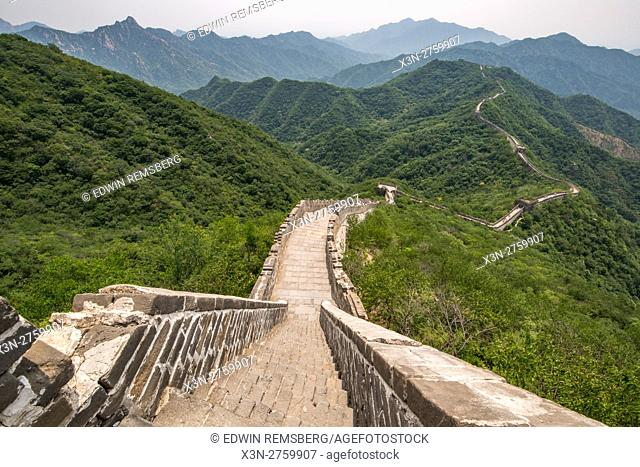 Mutianyu, China - Landscape view of the Great Wall of China. The wall stretches over 6,000 mountainous kilometers east to west across North China and through 15...