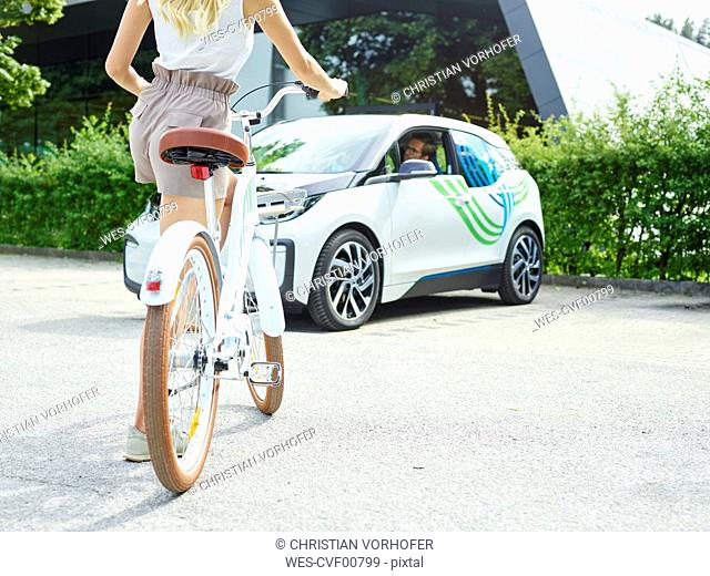 Woman with bicycle in front of electric car
