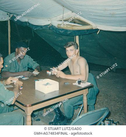 United States Servicemen playing cards at a table set up under a tent in their camp, two soldiers are wearing their full uniforms while a third is not wearing a...