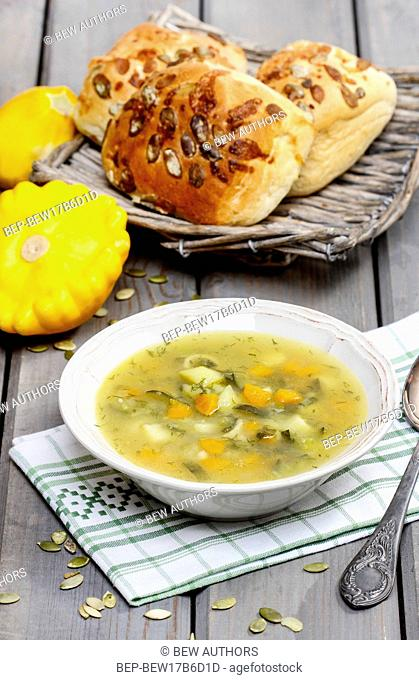 Vegetable soup on wooden table. Basket of fresh buns in the background