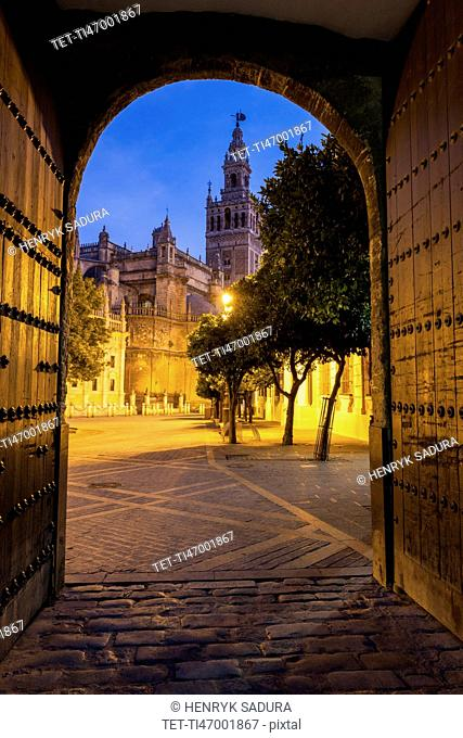 Spain, Andalusia, Seville, Arched corridor with Seville Cathedral (Cathedral of Saint Mary of the See) in background